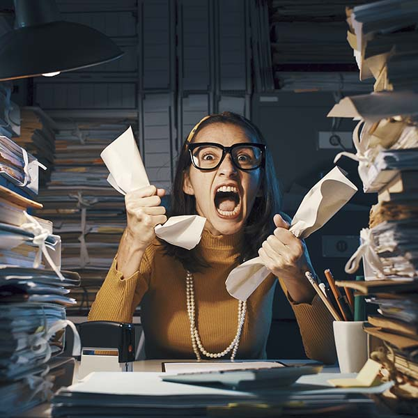 Angry stressed office worker overloaded with paperwork