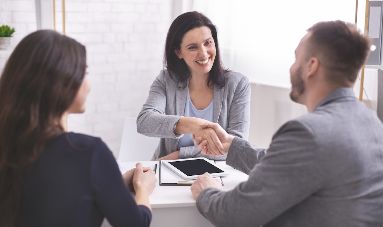 Smiling female insurance broker and young family shaking hands making purchase deal or investment, empty space